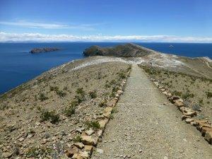 Le sentier droit entoure par le ciel et le lac bleu