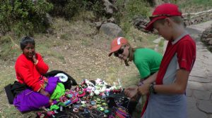 Kaia and Jake bargaining for woven bracelets.