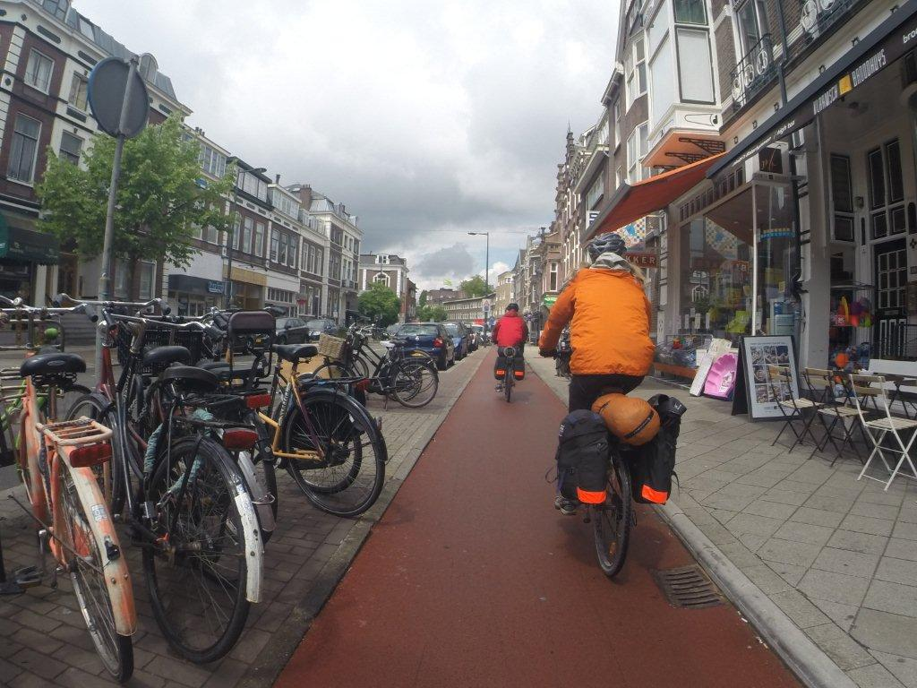 All over Holland, bike lanes are paved with red tar to make them obvious. In this particular place, the lane was separated from traffic by bike and car parking spaces.