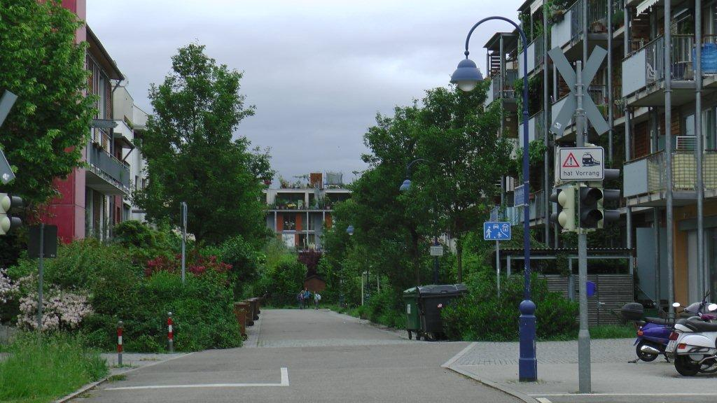 Freiburg has some car-reduced neighbourhoods like this one, Vauban.  Most streets are parking-free which means that cars can only stop for loading and unloading.  Neighbourhood garages are in 3 locations and provide enough space for all the residents cars.